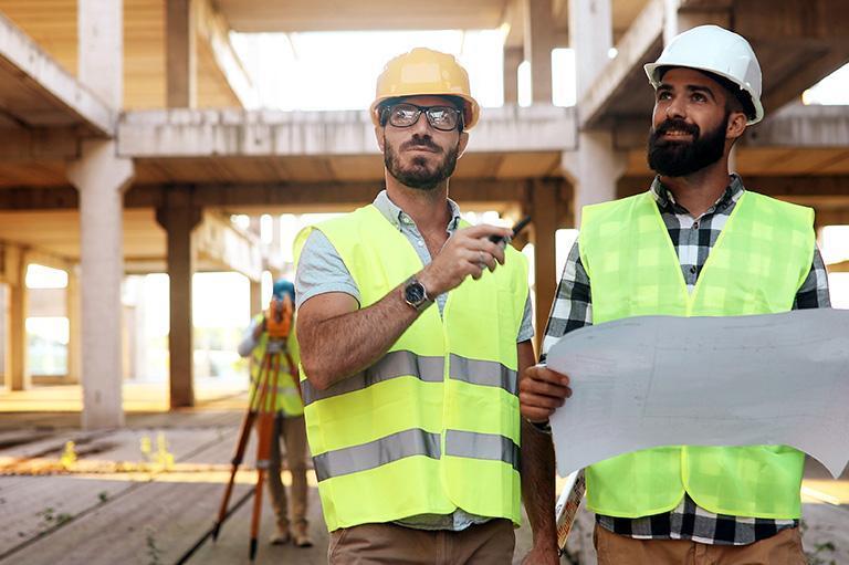 pracownicy budowy oglądają plany